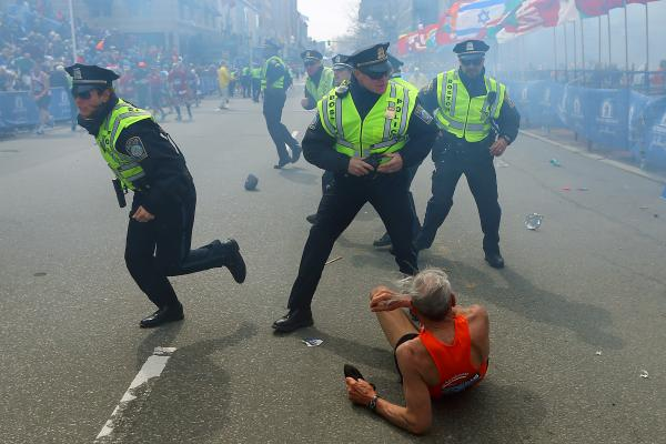 Police officers with their guns drawn hear a second explosion down the street near the finish line of the Boston Marathon. The first explosion knocked down a runner at the finish line. At least two people died and dozens were injured in the Monday blasts.