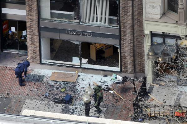 One of the blast sites on Boylston Street, near the finish line of the Boston Marathon, is investigated by two people in protective suits.