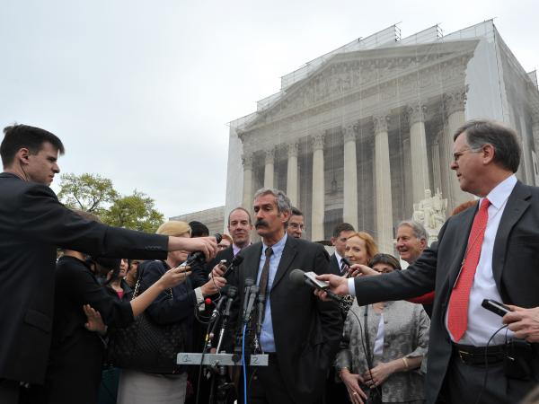 Medical geneticist Dr. Harry Ostrer (center) talks to the press outside the U.S. Supreme Court on Monday. The court heard oral arguments on the highly charged question of whether human genes can be patented.