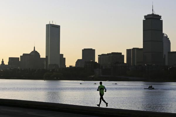 A runner heads down the banks of the Charles River in Cambridge, Mass., in front of the Boston skyline, at dawn Tuesday.