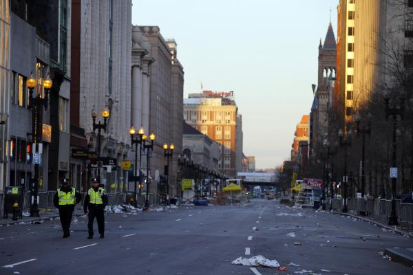 Two police officers walk down Boylston Street, away from the finish line of the Boston Marathon on Tuesday. Two bombs packed with ball bearings tore through crowds near the finish of the Boston Marathon, killing at least three people and injuring more than 150.