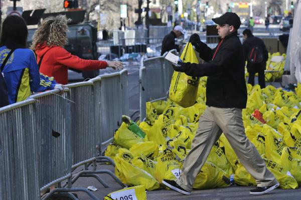 A worker returns a bag containing a runner's personal effects near the finish line.