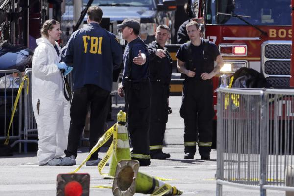 Boston firefighters speak with FBI agents and a crime scene photographer at the scene of the explosions.