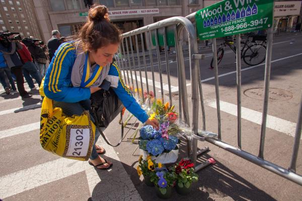 Marissa Irwin, a Boston College student and marathon runner, lays a flower against a police barricade near the site of the explosions.