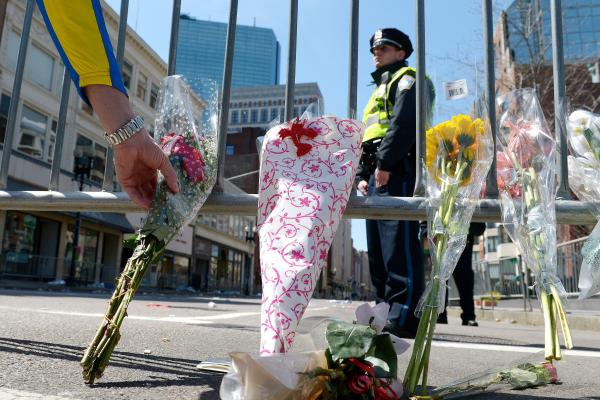 A man places flowers along a police barricade down the street from the finish line of the Boston Marathon. The blasts Monday killed at least three and injured more than 150.