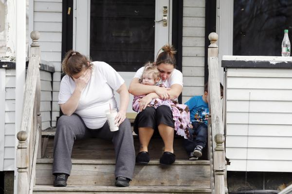Neighbors sit outside the house of Krystle Campbell's parents in Medford, Mass. Campbell was killed in Monday's explosions at the finish line of the Boston Marathon.