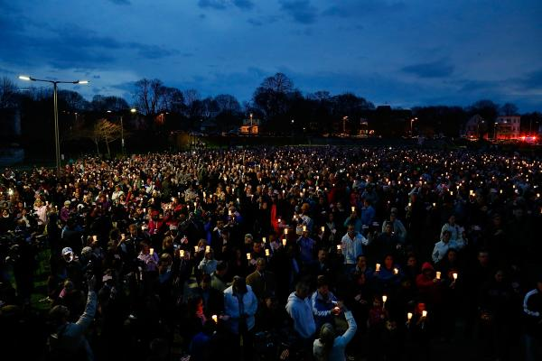 People gather with candles during a vigil at Boston's Garvey Park on Tuesday for Martin Richard.