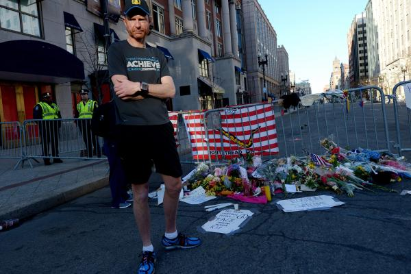 A man turns away from a temporary memorial on Boylston Street on Wednesday as an investigation continues into the dual bombings at the Boston Marathon.