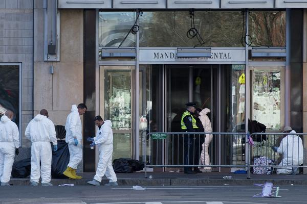 Evidence technicians work along Boylston Street on Wednesday as the investigation continues into the dual bombings at the finish line of the Boston Marathon. Three people were killed and about 180 were injured in the explosions near the finish line Monday.