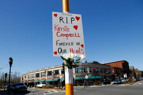 Flowers and a sign are left on a street post in Medford Square in remembrance of Krystle Campbell, 29, of Medford, Mass., who was killed by the bomb explosions at the Boston Marathon.