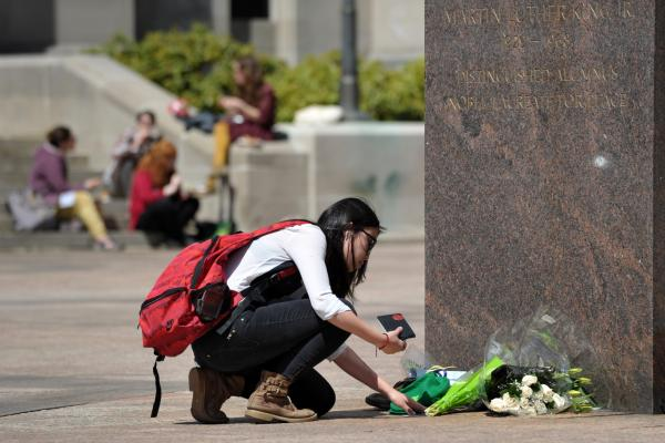 Journalism student Joy Liu places an Irish hat and note at a memorial site at Boston University on Wednesday. Lu Lingzi, a 23-year-old Chinese graduate student in statistics at Boston University, was one of the three people killed in the Boston Marathon bombings on Monday.