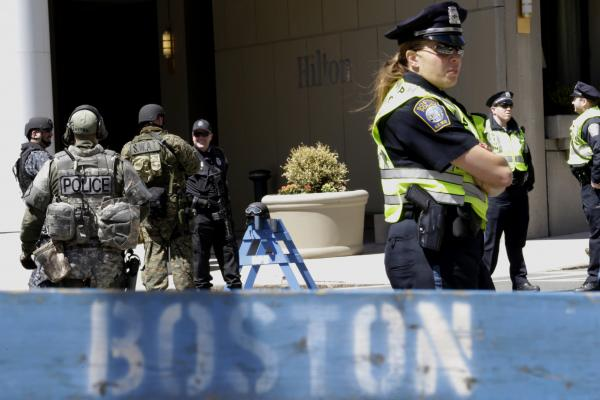 Officials in tactical gear stand guard behind a Boston Police Department barricade near the site of the Boston Marathon explosions.