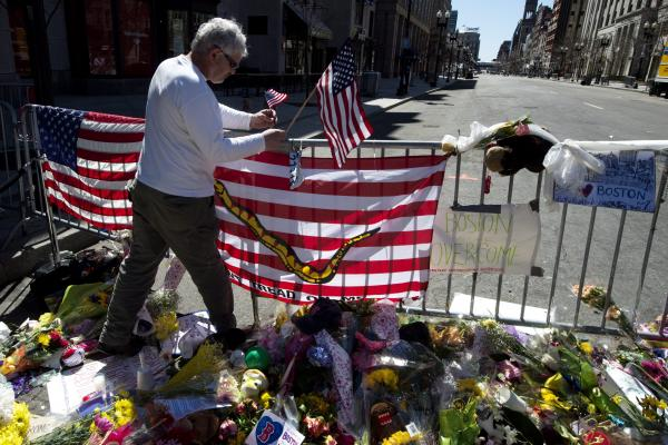 A man adds an American flag to a memorial on Boylston Street as an investigation continues into the dual bombings. Three people were killed and over 100 were injured when two bombs exploded on Monday at the finish line of the marathon.