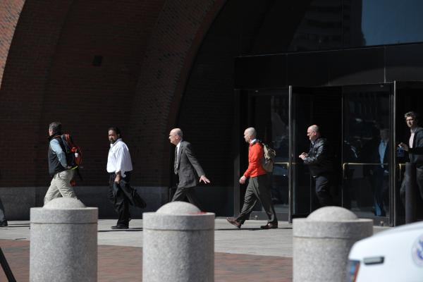 Employees from the Moakley Federal Courthouse in Boston leave under orders to evacuate because of a bomb threat. After about an hour, the building was deemed clear and staff were allowed back inside.