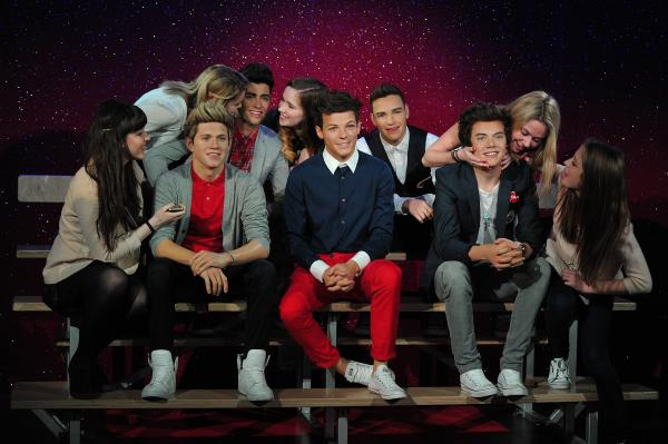 Fans pose for pictures with waxwork models of English-Irish boy band 'One Direction' at Madame Tussauds in London this week.