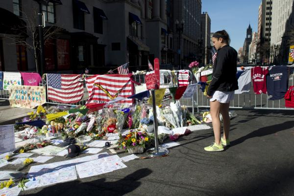 Alice Binns looks at a makeshift memorial on the Boston Marathon route. Binns ran in the marathon and said she had just finished the race when a bomb went off.