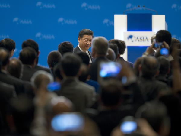 China's President Xi Jinping (center back) walks to his seat as he arrives at the opening ceremony of the annual Boao Forum in Boao, in southern China's Hainan province, on Sunday.