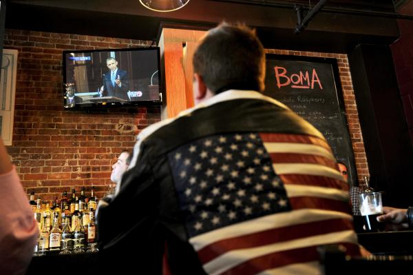 A man at the BoMA restaurant across the street from the Cathedral of the Holy Cross watches Obama's speech during the memorial.