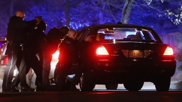 Police with guns drawn search for one of the Boston Marathon suspects early Friday in Watertown, Mass.