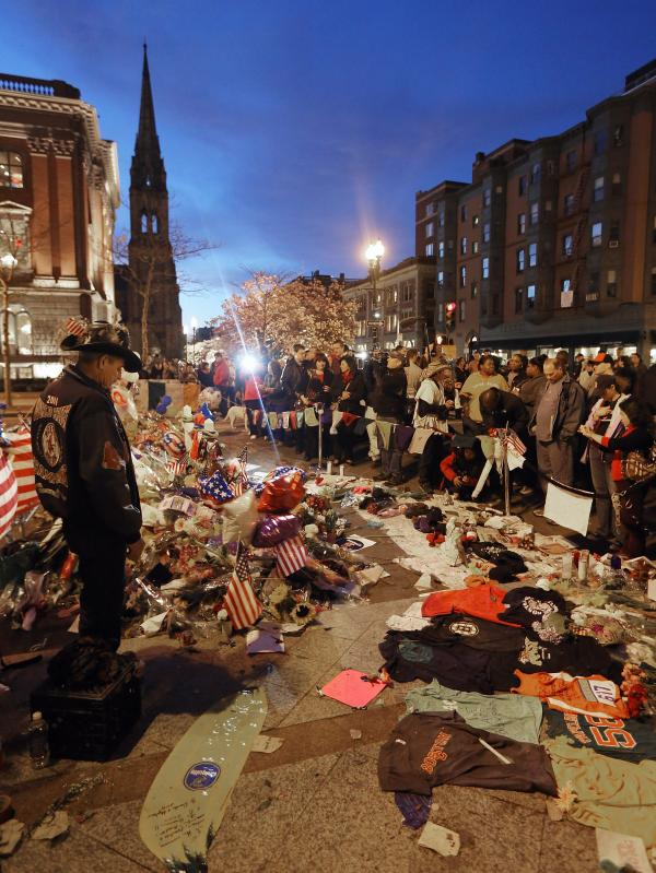People gather at a makeshift memorial for victims of the Boston Marathon bombings at the edge of the still-closed section of Boylston Street. The surviving suspect in the case, Dzhokhar Tsarnaev, remains in the hospital.