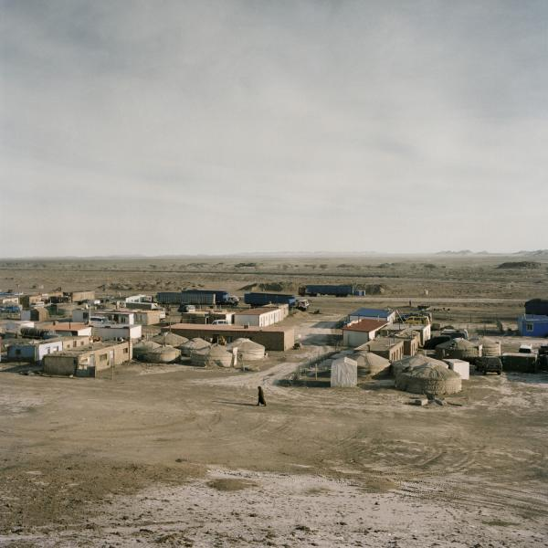 A woman walks in an outpost for coal delivery at the border with China. Mongolia, Gobi, White Mountain outpost, 2013.