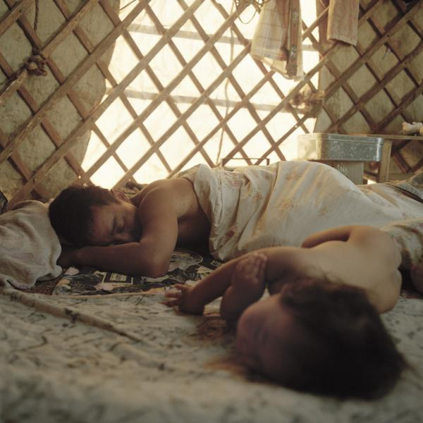 Tuvshinbayar sleeps with his son, Tuyshintugs, after a morning working with his camels. Mongolia, Gobi, Omongov, 2012.