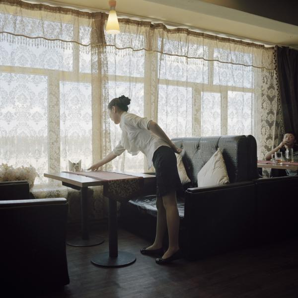 A waitress works at the Broadway restaurant, the only restaurant for foreigners in the district. Mongolia, Gobi, Tsogttsetsii sum, 2012.