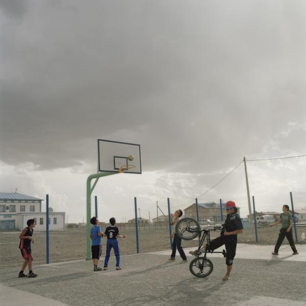 Young boys play in the only public place in the village — the basketball field of the public school. Mongolia, Gobi, Tsogttsestii sum, 2012.