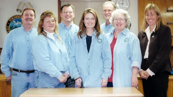 Sarah Palin (center) stands with the Wasilla, Alaska, City Council for a portrait in 1998. In 1992, then-Mayor John Stein recruited Palin as a moderate counterweight to the growing anti-government, anti-tax movement. By 1996, Palin challenged Stein in the race for mayor — and won.