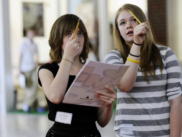Kate Haynes (left) and Samantha Jensen watch the stock tickers and debate what to select for their investments while participating in Junior Achievement's Finance Park program in Fairfax County, Va.