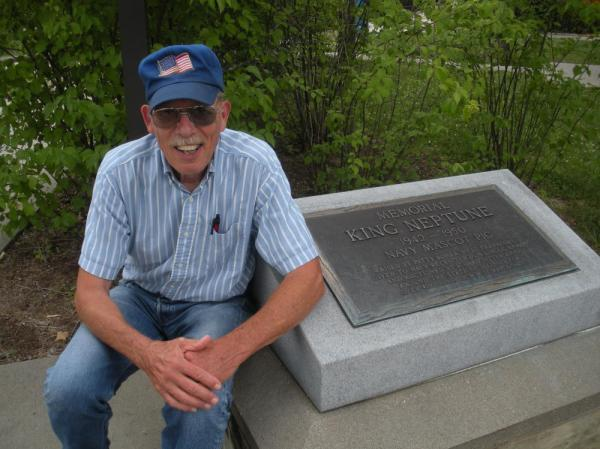 "Jim Goddard, a retired shop owner from Anna, Ill., sits next to a plaque dedicated to his grandpa's pig, King Neptune. The plaque reads: ""King Neptune: 1942 to 1950. Navy Mascot Pig."""