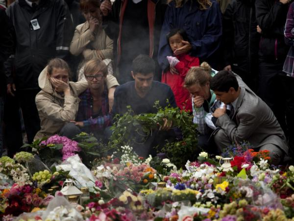 People pay tribute to victims of the twin attacks before a memorial service at Oslo Cathedral in Norway on Sunday. At least 93 were killed and nearly 100 were wounded in Friday's attacks.
