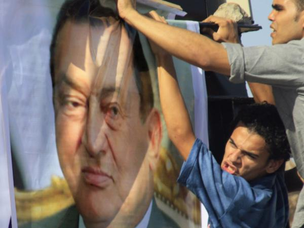 An Egyptian pro-Mubarak protester erects a poster of the ousted president on Wednesday outside the police academy in Cairo, where Hosni Mubarak, his two sons and others face trial on charges they ordered the use of lethal force against protesters during Egypt's 18-day uprising. Some 850 protesters were killed.