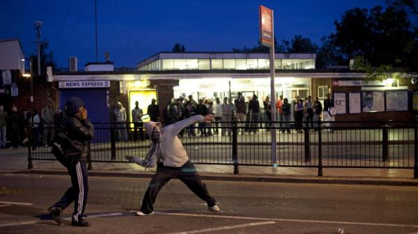 Youths throw bricks at police in this Sunday, Aug. 7, 2011 photo  during unrest in Enfield, north London. Nearly 1,200 people have been arrested since the riots erupted Saturday, mostly poor youths from a broad section of Britain's many races and ethnicities.  Britain is bitterly divided on the reasons behind the riots.
