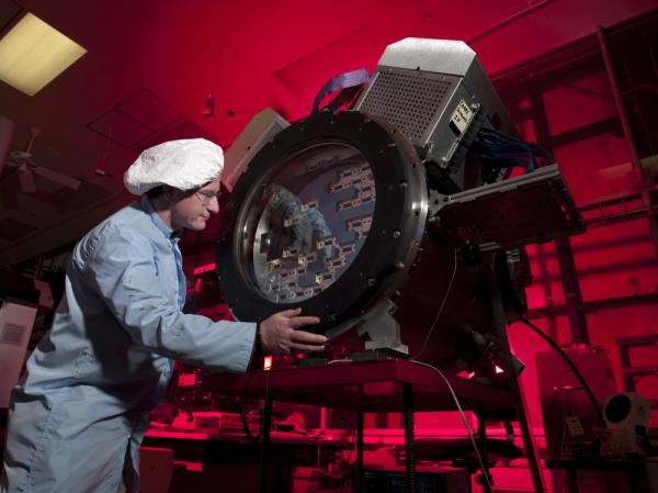 Fermilab scientist Tom Diehl works on the heart of the Dark Energy Camera.