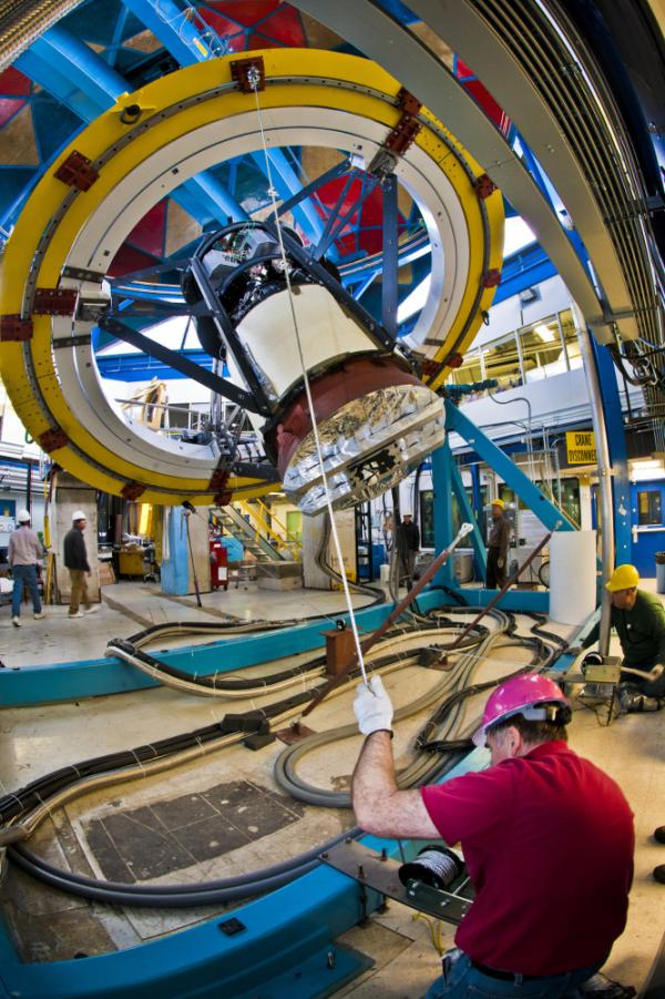 Workers test the fitting of the camera on a simulator device at Fermilab, outside Chicago. The camera will be installed on the Blanco telescope high in the Chilean mountains.