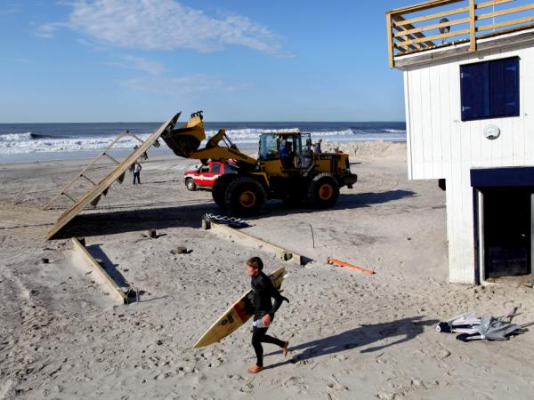 A surfer in Long Beach, N.Y., passes heavy machinery Monday that was removing the remnants of a lifeguard shack that was knocked off its footing during Irene.