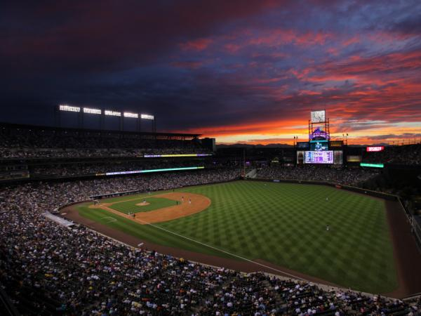 The sun sets over Coors Field in Denver. While summer nights are perfect for baseball, late-season games can get a little chilly.