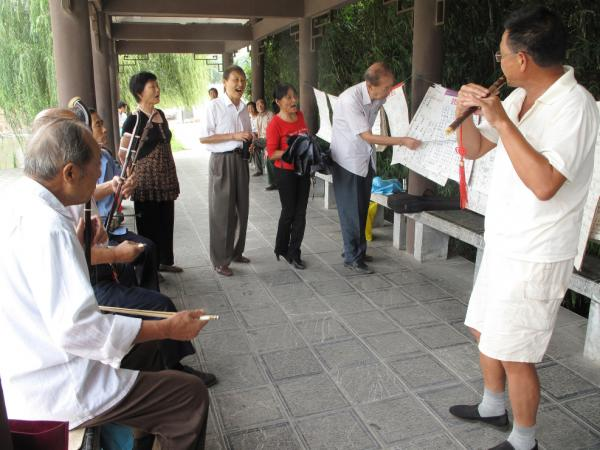 "Retirees in a Chaohu park play the song ""Chaohu Is Good"" on the <em>erhu</em>, a traditional Chinese instrument. So far, opinions are split on whether dividing the city will be good for their future."