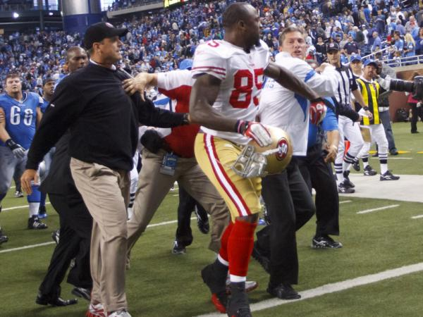 <p>Harbaugh (in dark cap and jacket) and Schwartz (in white jacket with blue stripes) are separated by the 49ers' Venron Davis (85).</p>