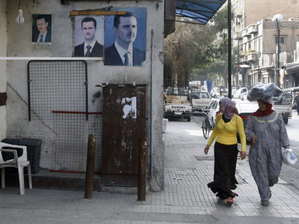 <p>Syrian women stroll past posters of President Bashar Assad in Damascus on Monday. Assad has relied heavily on his security forces as he battles an uprising now in its eighth month. </p>
