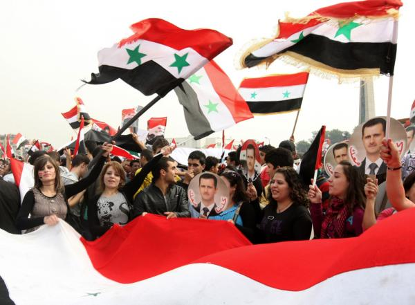 <p>Tens of thousands of people rally in support of Syrian President Bashar al-Assad in Damascus on Wednesday.</p>