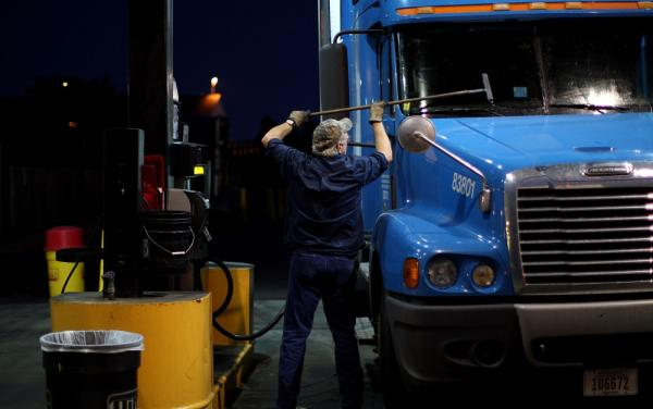 <p>A truck driver cleans his windshield at a filling station in Milford, Conn. The long hours, weeks away from home and mediocre pay contribute to the trucking industry's shortage of an estimated 125,000 drivers.</p>