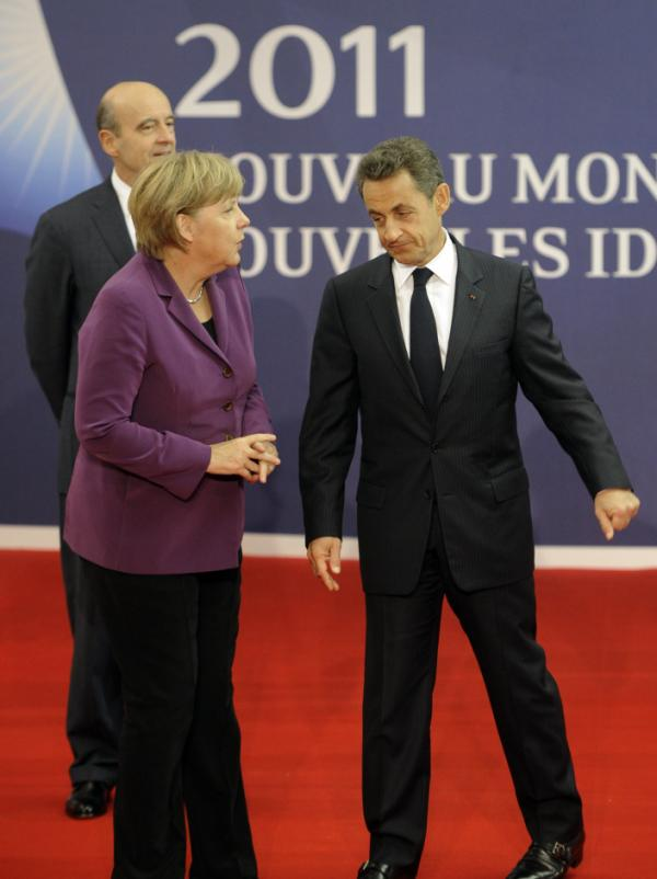 German Chancellor Angela Merkel talks to French President Nicolas Sarkozy on the eve of the G-20 summit in Cannes, France, on Wednesday. The European economic crisis is taking center stage at the summit.