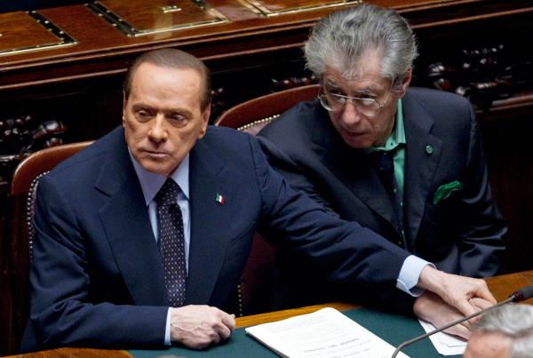 Italian Premier Silvio Berlusconi, left, holds the hand of Reforms Minister Umberto Bossi during a must-watched vote at the Lower Chamber, in Rome, Tuesday, Nov. 8, 2011.