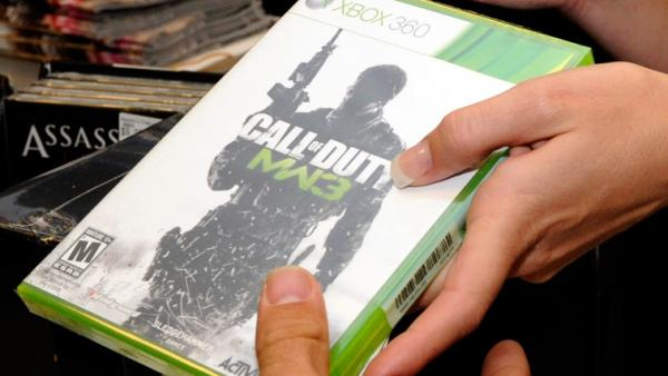 "A customer buys a copy of ""Call of Duty: Modern Warfare 3"" for the Xbox 360 during a launch event for the highly anticipated video game."