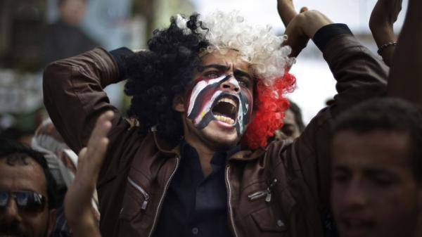 A protester with Yemeni, Egyptian, Libyan and Syrian flags painted on his face chants slogans during a demonstration Wednesday in Sanaa, Yemen, against a deal that grants immunity for President Ali Abdullah Saleh.