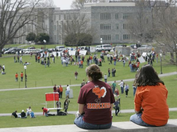 Students sit at the Virginia Tech campus on April 18, 2007, two days after a student killed 32 people and himself. FBI victim specialists span out to help in the wake of crimes like the Virginia Tech massacre.