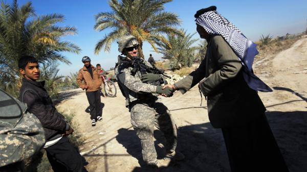 U.S. Army Lt. Adam Wilson from Ontario, Calif., shakes hands with Sheik Mahmood Al-Ghizzi, possibly for the last time, on Dec. 5 in Nasiriyah, Iraq. The two men met for a final lunch as the U.S. military prepares to leave Iraq after a nearly nine-year presence.