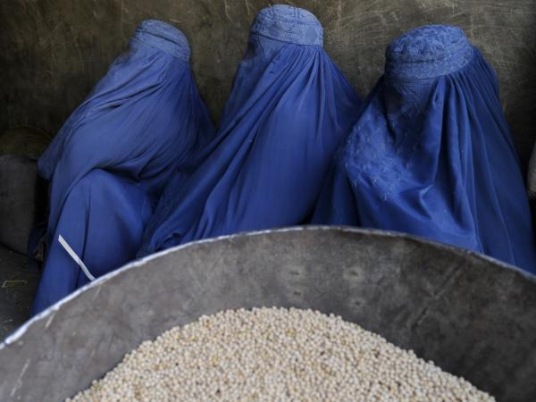 Burqa-clad Afghan women wait to buy chickpeas from a shop in Kabul earlier this year.